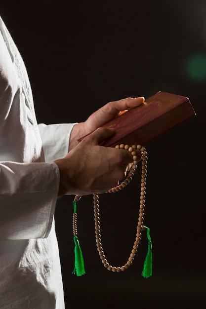 Mens die in traditionele arabische kleren koran en gebedparels houdt Premium Foto