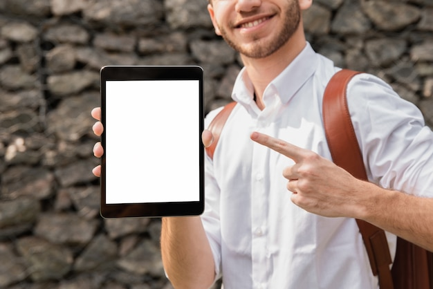 Mens die in wit overhemd op zijn tablet richt Gratis Foto