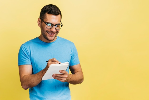 Mens die in zijn notitieboekje schrijft Gratis Foto