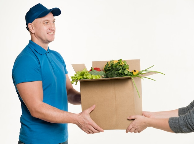 Mens die kartondoos met voedsel levert Gratis Foto