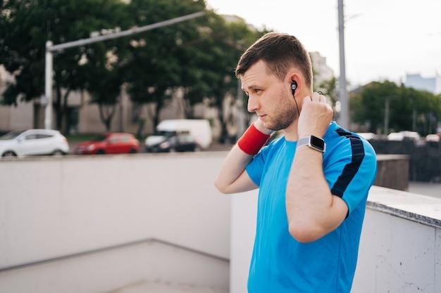 Mens die klaar stadstraining krijgt die oortelefoons schikt Gratis Foto