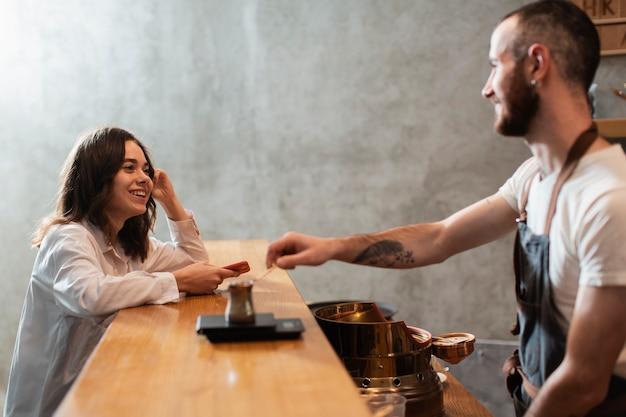 Mens die koffiepot op bar met klant zetten Gratis Foto