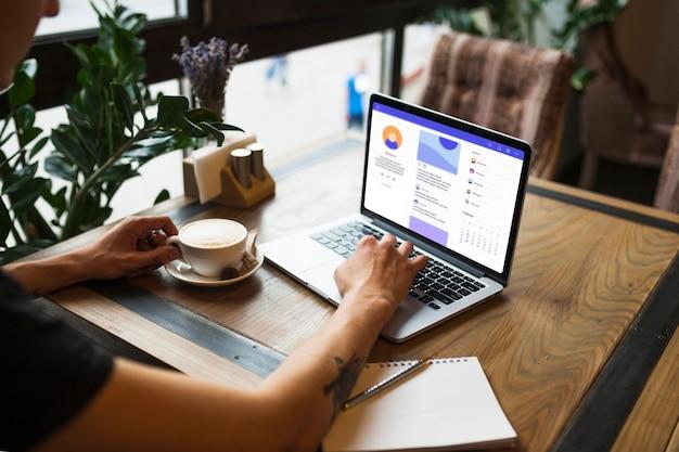 Mens die laptop in koffie met behulp van Gratis Foto