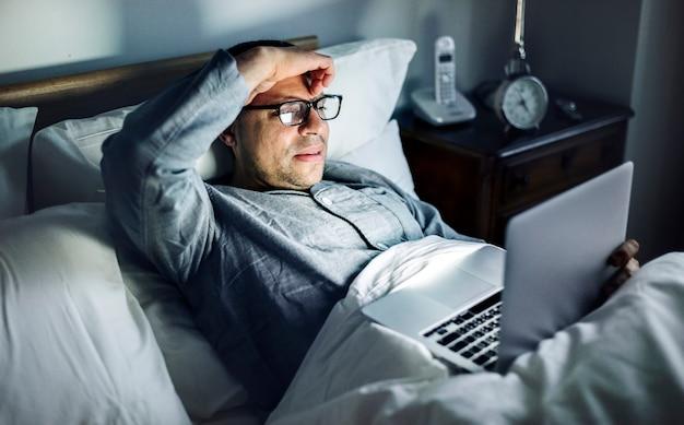 Mens die laptop op een bed met behulp van Premium Foto