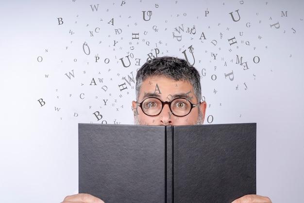 Mens die met glazen een notitieboekje met brieven in de lucht houdt Premium Foto