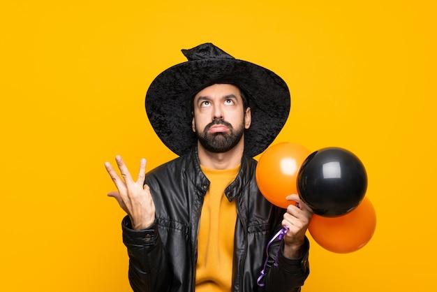 Mens die met heksenhoed zwarte en oranje luchtballons voor halloween-partij houdt gefrustreerd door een slechte situatie Premium Foto