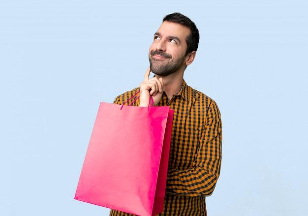 Mens die met het winkelen zakken een idee denken terwijl omhoog het kijken Premium Foto