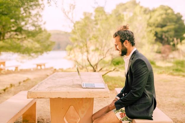 Mens die met laptop in zonnig park werkt Gratis Foto