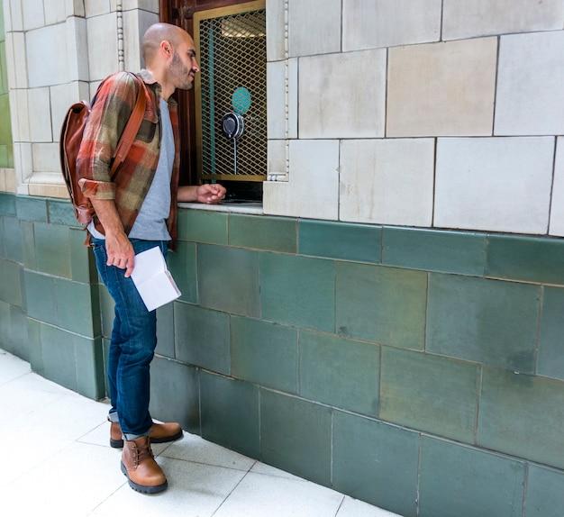 Mens die met rugzak stadsmeningen controleert Gratis Foto