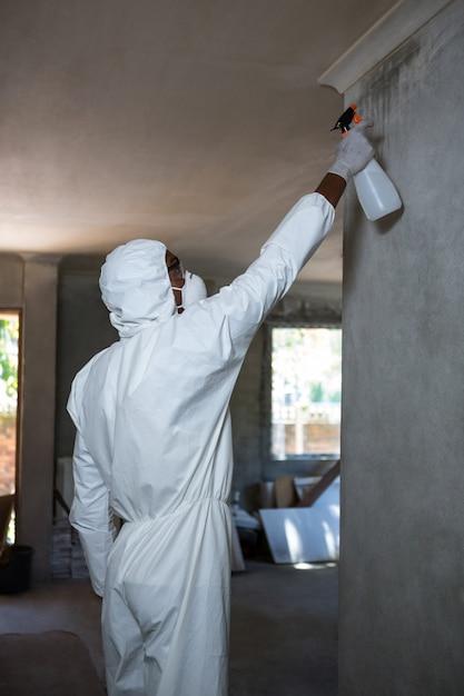 Mens die ongediertebestrijding op een muur doet Premium Foto