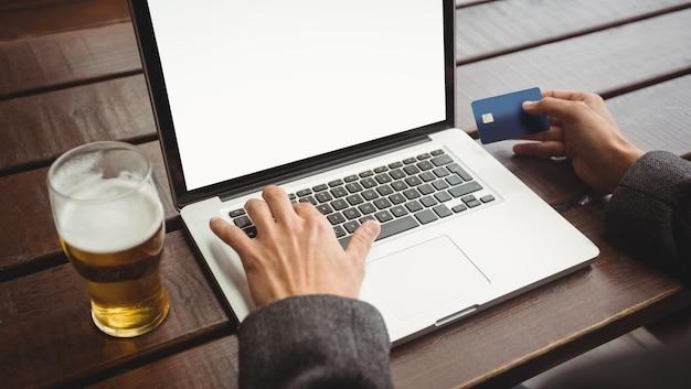 Mens die online het winkelen met creditcard op laptop doet Gratis Foto