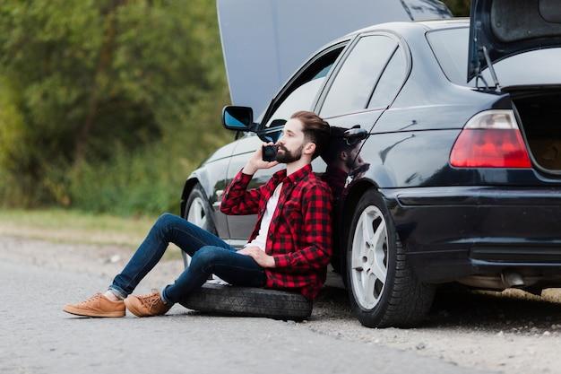 Mens die op auto leunt en op telefoon spreekt Gratis Foto