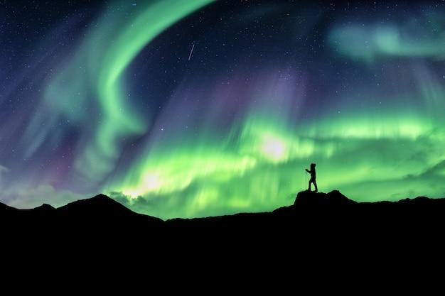 Mens die op berg met noordelijke lichtenexplosie wandelen Premium Foto