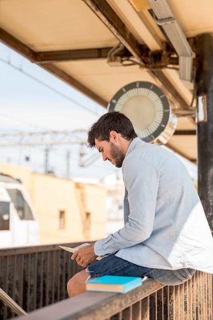 Mens die op een kaart kijkt en op trein wacht Gratis Foto