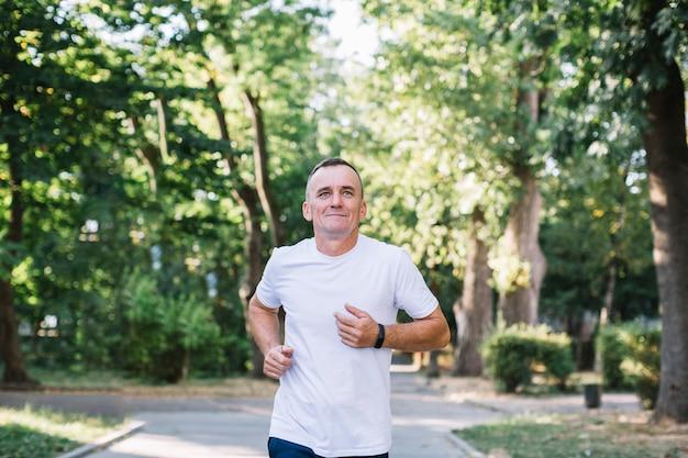 Mens die op een steeg in het park loopt Gratis Foto
