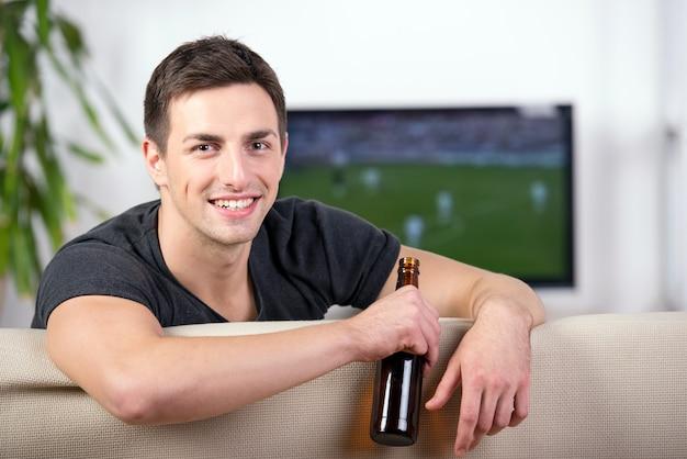 Mens die op een voetbalspel op bank met een bier let. Premium Foto