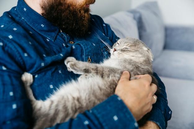 Mens die op handen houdt die kat slapen Gratis Foto