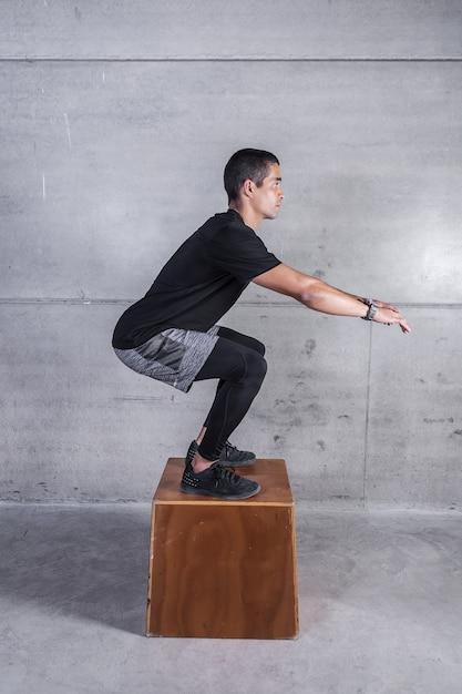Mens die op houten blok hurkt Premium Foto