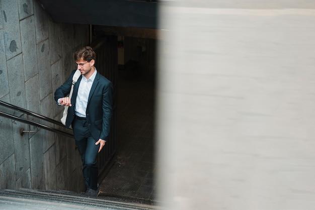 Mens die op metrotrap het letten op tijd loopt Gratis Foto