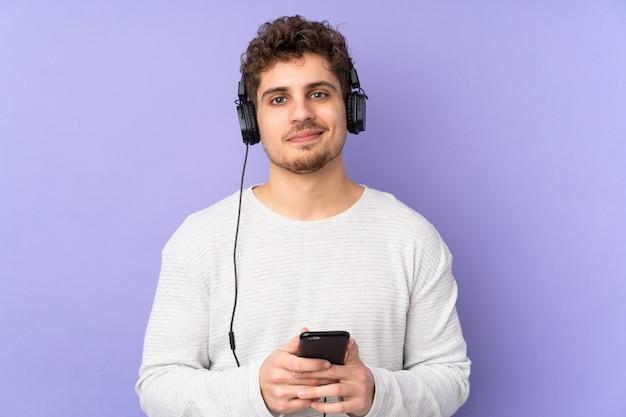 Mens die op purpere muur het luisteren muziek met mobiel wordt geïsoleerd en voorzijde kijkt Premium Foto
