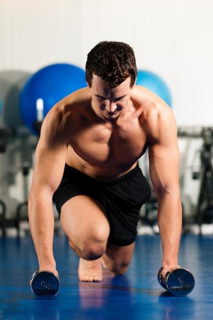 Mens die opdrukoefeningen in gymnastiek doet Premium Foto
