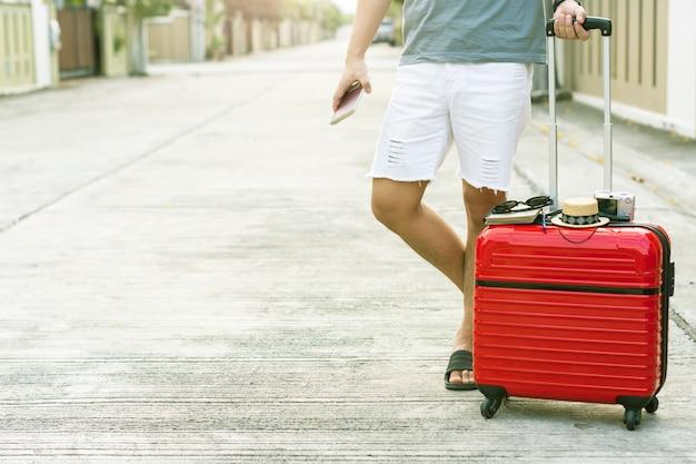 Mens die rode bagage met paspoort op vage stadsachtergrond houdt Premium Foto