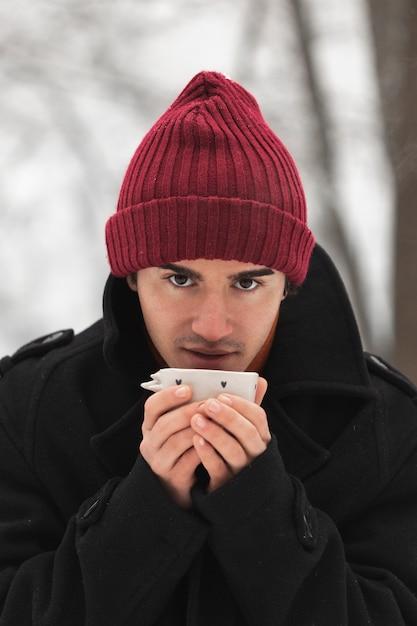 Mens die rode hoed draagt die van een kop thee nipt Gratis Foto