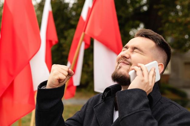 Mens die smartphone met erachter vlaggen van polen gebruiken Premium Foto