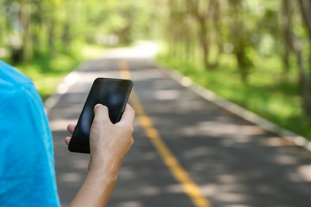 Mens die smartphone op een weg in het park gebruikt Premium Foto