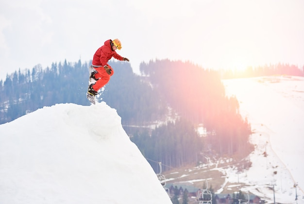 Mens die snowboarder vanaf de bovenkant van de sneeuwheuvel met snowboard in de avond bij zonsondergang springt Premium Foto
