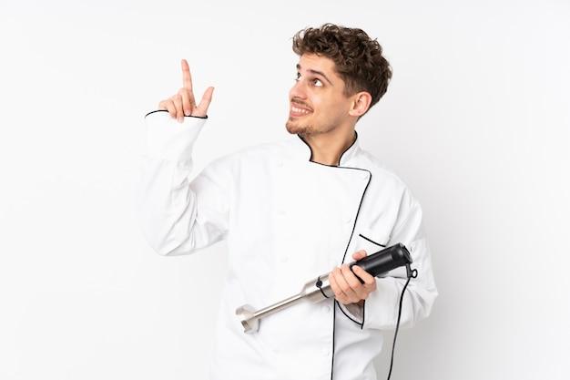 Mens die staafmixer op witte muur met behulp van die met de wijsvinger een groot idee richten Premium Foto