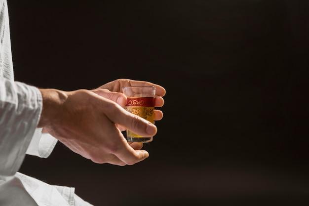 Mens die traditionele thee zwarte achtergrond houdt Premium Foto