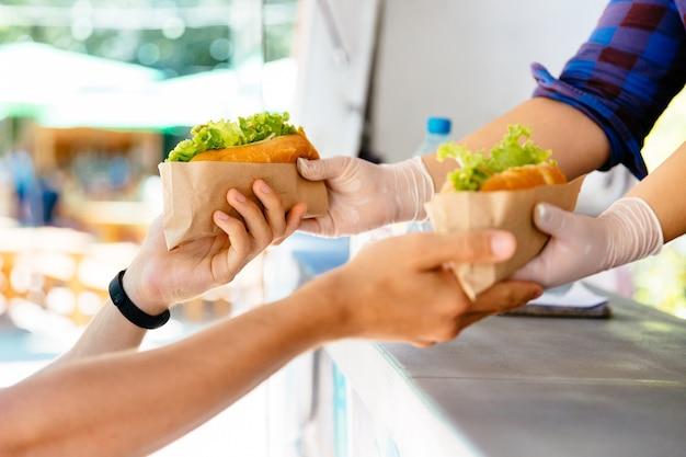 Mens die twee hotdog in een kiosk kopen, in openlucht. straatvoedsel. close-up weergave. Gratis Foto
