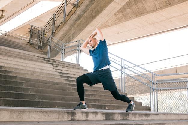 Mens die uitrekkende oefeningen op concrete trappen uitvoert Gratis Foto