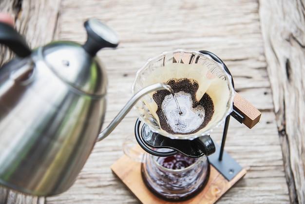 Mens die verse koffie in uitstekende koffiewinkel druppelen Gratis Foto