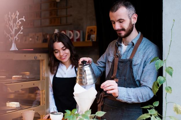 Mens die werknemer toont hoe te om koffie in filter te gieten Gratis Foto