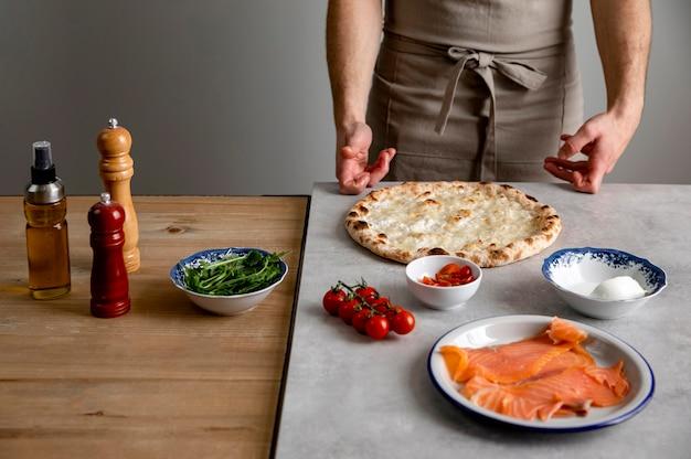 Mens die zich dichtbij gebakken pizzadeeg en ingrediënten bevindt Gratis Foto