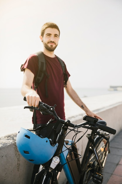 Mens die zich naast e-fiets bevindt en camera bekijkt Gratis Foto