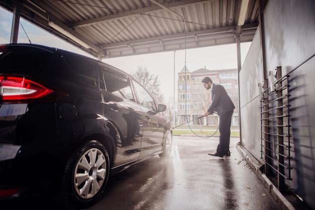 Mens die zijn auto in autowasserette schoonmaken. Premium Foto