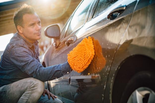 Mens die zijn auto met washandschoen wast Premium Foto