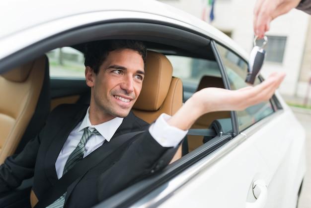 Mens die zijn autosleutel neemt Premium Foto