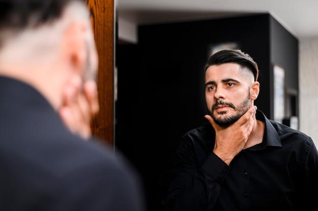 Mens die zijn baard in de spiegel controleert Gratis Foto