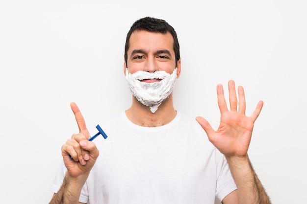 Mens die zijn baard over geïsoleerd wit scheert dat zes met vingers telt Premium Foto