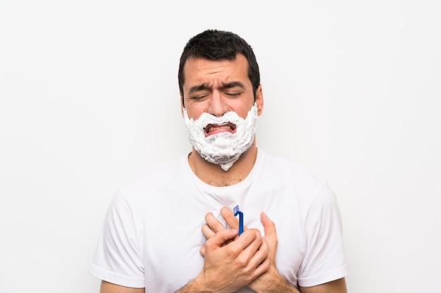 Mens die zijn baard over geïsoleerde witte muur scheert die pijn in het hart heeft Premium Foto