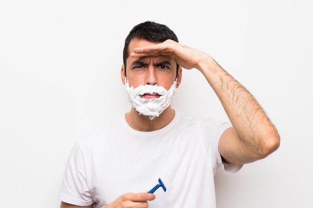 Mens die zijn baard over geïsoleerde witte muur scheert die ver weg met hand kijkt om iets te kijken Premium Foto