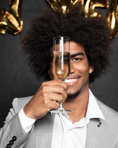 Mens die zijn gezicht behandelt met een glas champagne Gratis Foto