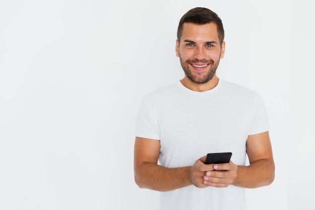 Mens die zijn telefoon op handen en witte achtergrond heeft Gratis Foto
