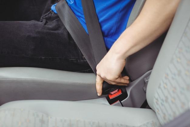 Mens die zijn veiligheidsgordel in een bestelwagen gespt Premium Foto
