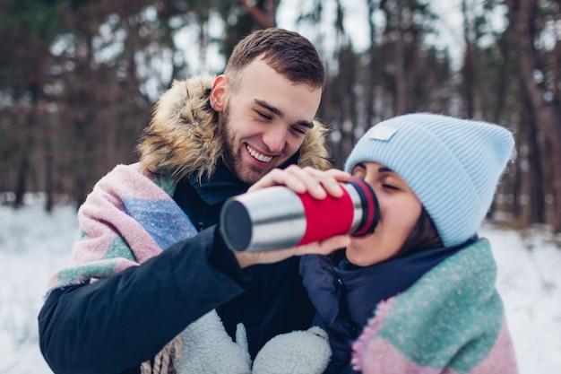 Mens die zijn vriendin hete thee geeft om in thermoskankop te drinken. houdend van paar die samen in de winterbos lopen. Premium Foto