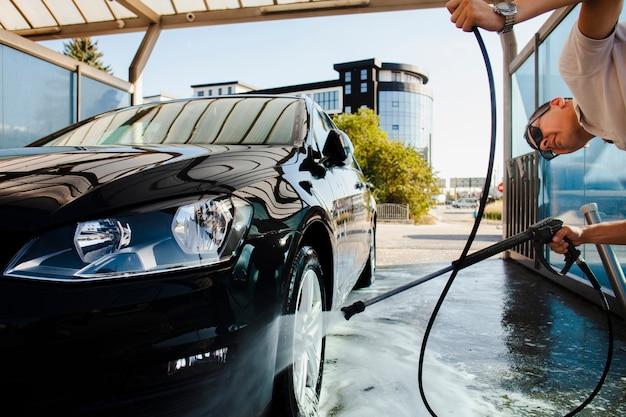 Mens die zorgvuldig een autowiel schoonmaakt Premium Foto